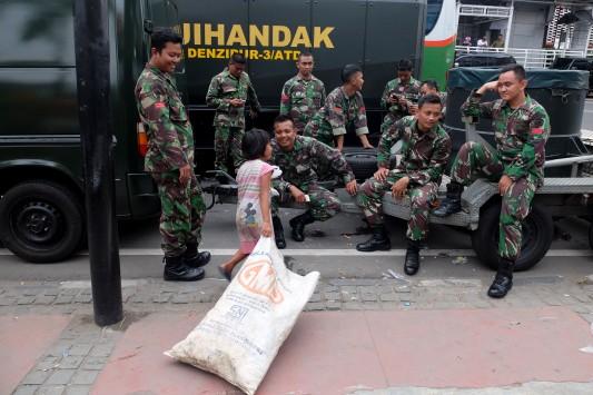 Pasukan TNI AD bercanda dengan seorang anak jalanan usai aksi teror di kawasan Thamrin, Jakarta, Kamis, 14 Januari 2016. - The Jakarta Post / Jerry Adiguna