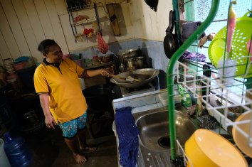 Ida Padua (38 tahun) menggoreng keripik tortila kepiting olahannya di rumah keluarganya di kampung Argosigemerai, Teluk Bintuni, Papua Barat, 1 April 2019. Melalui usaha pengolahan keripik tortila kepiting dan cheese stick udang yang dilakukannya, Ida Padua berharap dapat memperbaiki kondisi perekonomia keluarga dan kelompoknya. - JP/Jerry Adiguna